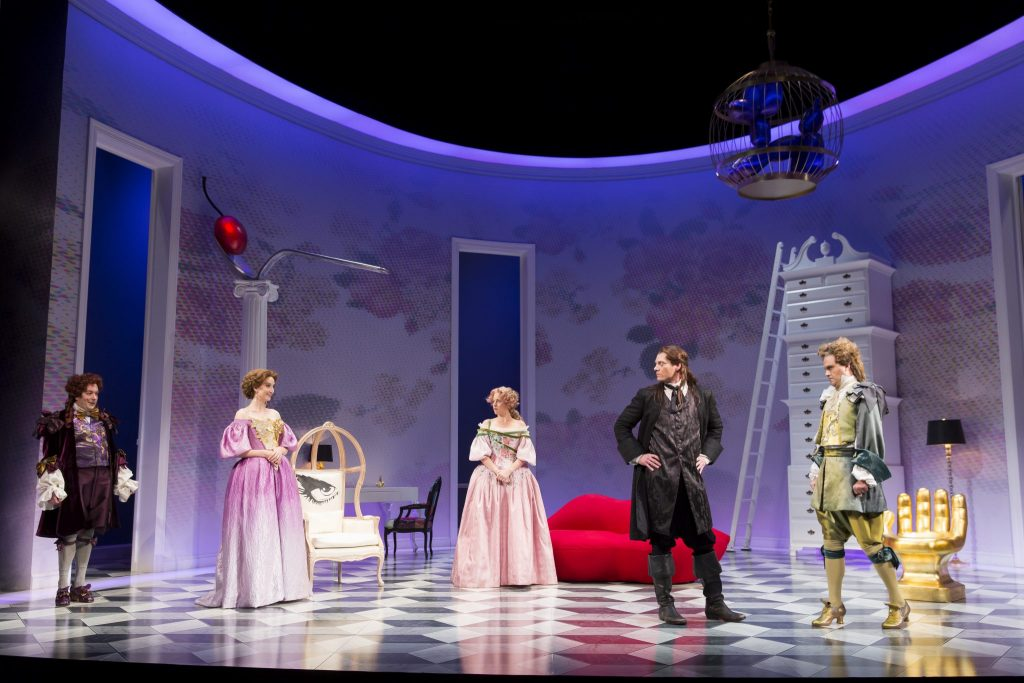 The cast of The School For Lies featuring Alexander Dodge's lush aqua blue parlor setting.