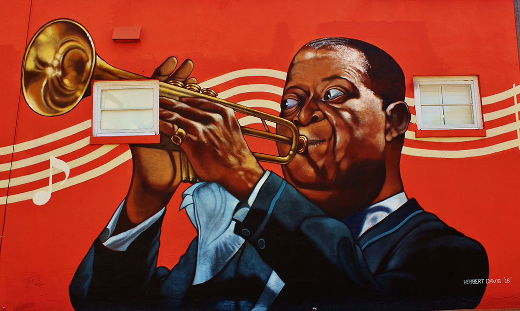 Images of the Great New Orleans horn player 'Satchmo' grace the sidewall on 9th street as you enter the FREE parking lot, and out door patio!