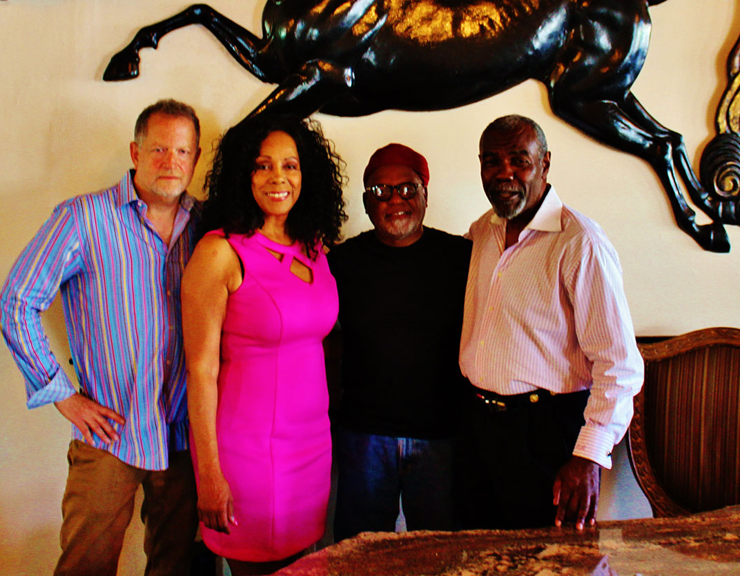 Band members Michael Ross, vocalist Katt Hefner and vocal percussionist Ed Johnson join the Host Elihu Braveboy take a moment before closing for a group picture under the recycled fiberglass stallion.